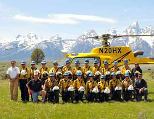 Photo of Teton Interagency Helitack crew with helicopter and Tetons in background